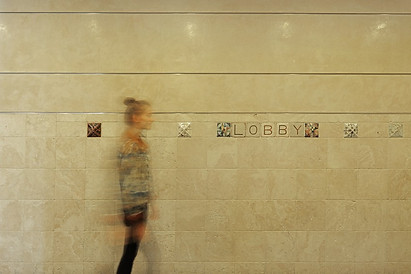 Woman walking by lobby sign.