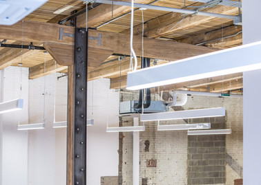Close-Up of wood structural beams and hanging light fixtures.
