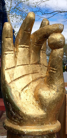 A giant golden hand with a golden ball clasped betweenthe thumb and middle finger, suggestive of a sutra, with blue sky and branches behind
