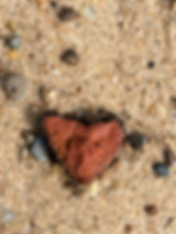 A piece of red brick in the shape of a heart laying on beach sand wit small rick and bits of seaweed here and there.
