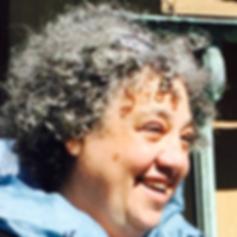 Dina Stander in profile, her face sunlit, her smile radiant