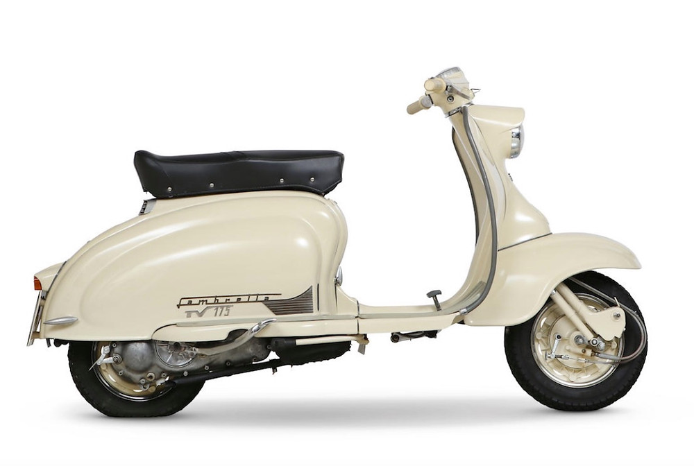 A side view of a white 2 wheeled (vintage, circa 1956-59) Lambretta scooter with a seat big enough for one and a half people.