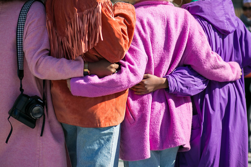 we see the backs of four women in colorful purple pink and orange coats with their arms around each other's waists, the photo evokes warmth and affection