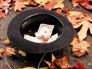 a bowler hat turned like a bowl to hold dollars and change, on a leafy sidewalk