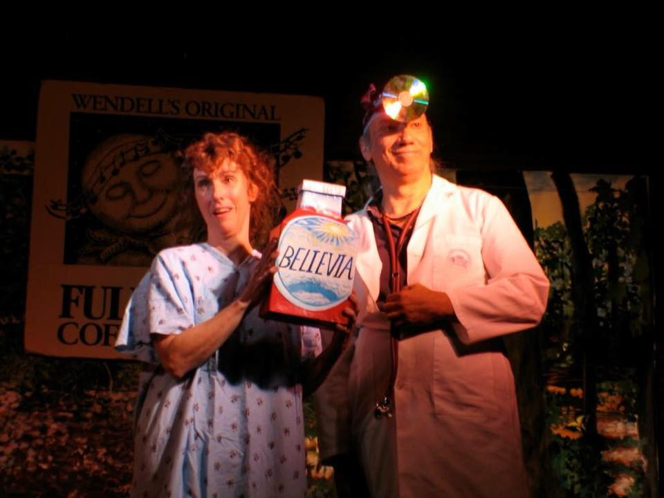 Two actors on stage, a patient and a doctor, holding giant milk carton labeled Believia
