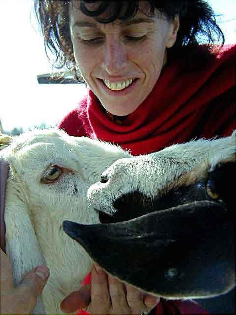 Close up of woman in red, holding the faces of two goats and smiling.