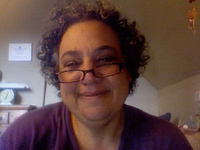 This is a picture of Dina Stander, her face is framed in an oval shapd frame. She is looking over her glasses and smiling. She has dark curly hair and looks friendly.