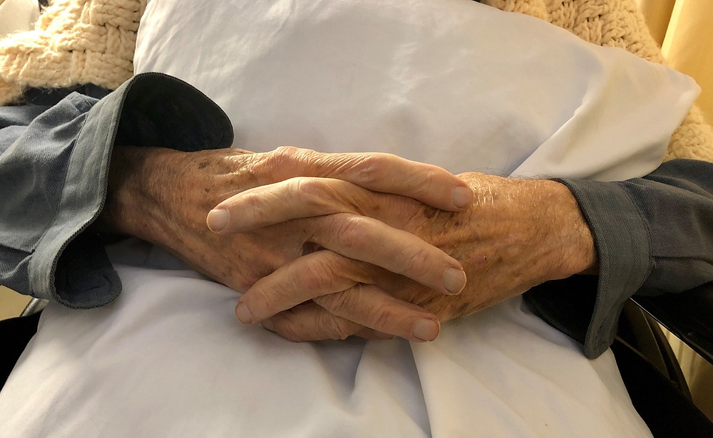 two hands together, with long wrinkled fingers intertwined, above a lap pillow.