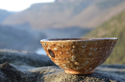 Closeup of a brown ceramic bowl wih whte spots on the glaze, set on a rock with a backdrop of majestic mountains