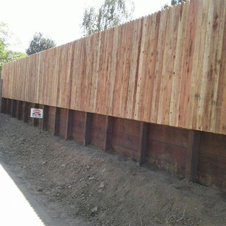 Retainer wall integrated with fence