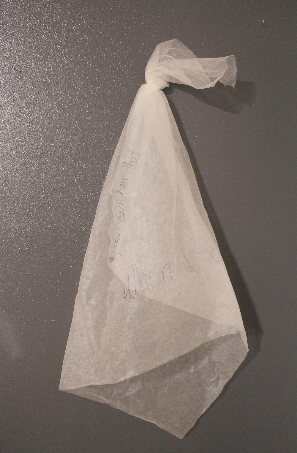 A transparent white handkerchief, knotted at the top and hanging from a gray wall.