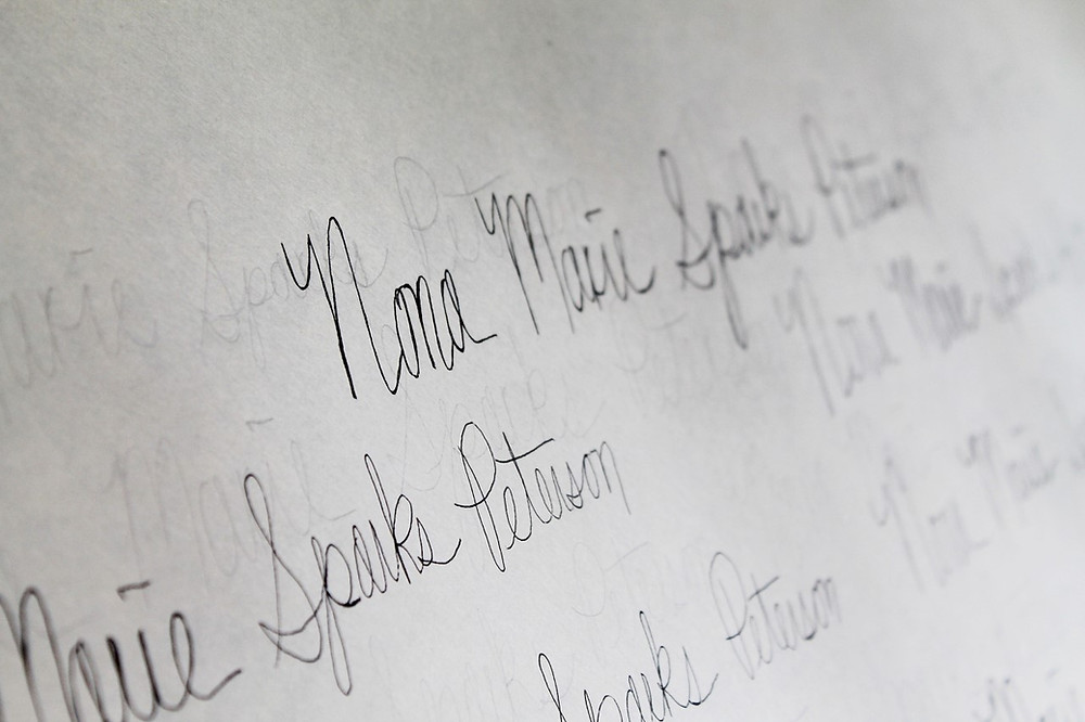 handwritten cursive on a white sheet of paper, written diagonally. the specific words are unreadable.