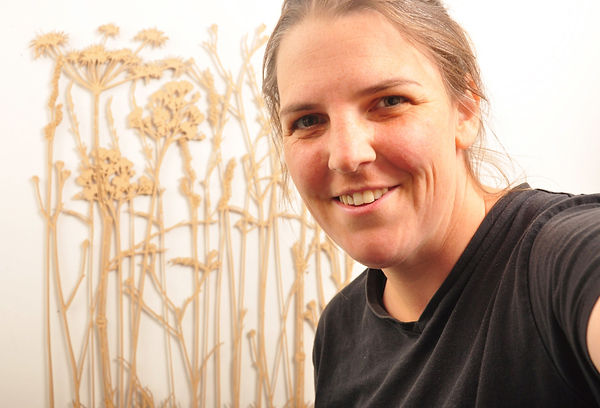A photograph of Martha Ellis who is the brains and brawn behind Mash & Co. She has a piece of her own art work in the background. It is complex and intricate drawing of wild grasses.