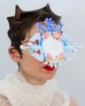 Lorca wears house of bun headpiece III, an acrylic mirrored mask with flower and sky motifs. Their hair is digitally enhanced and they are wearing a lace collar.