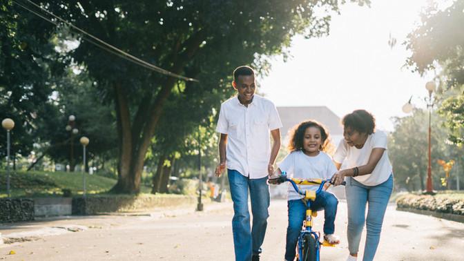 Family pushing girl on bike