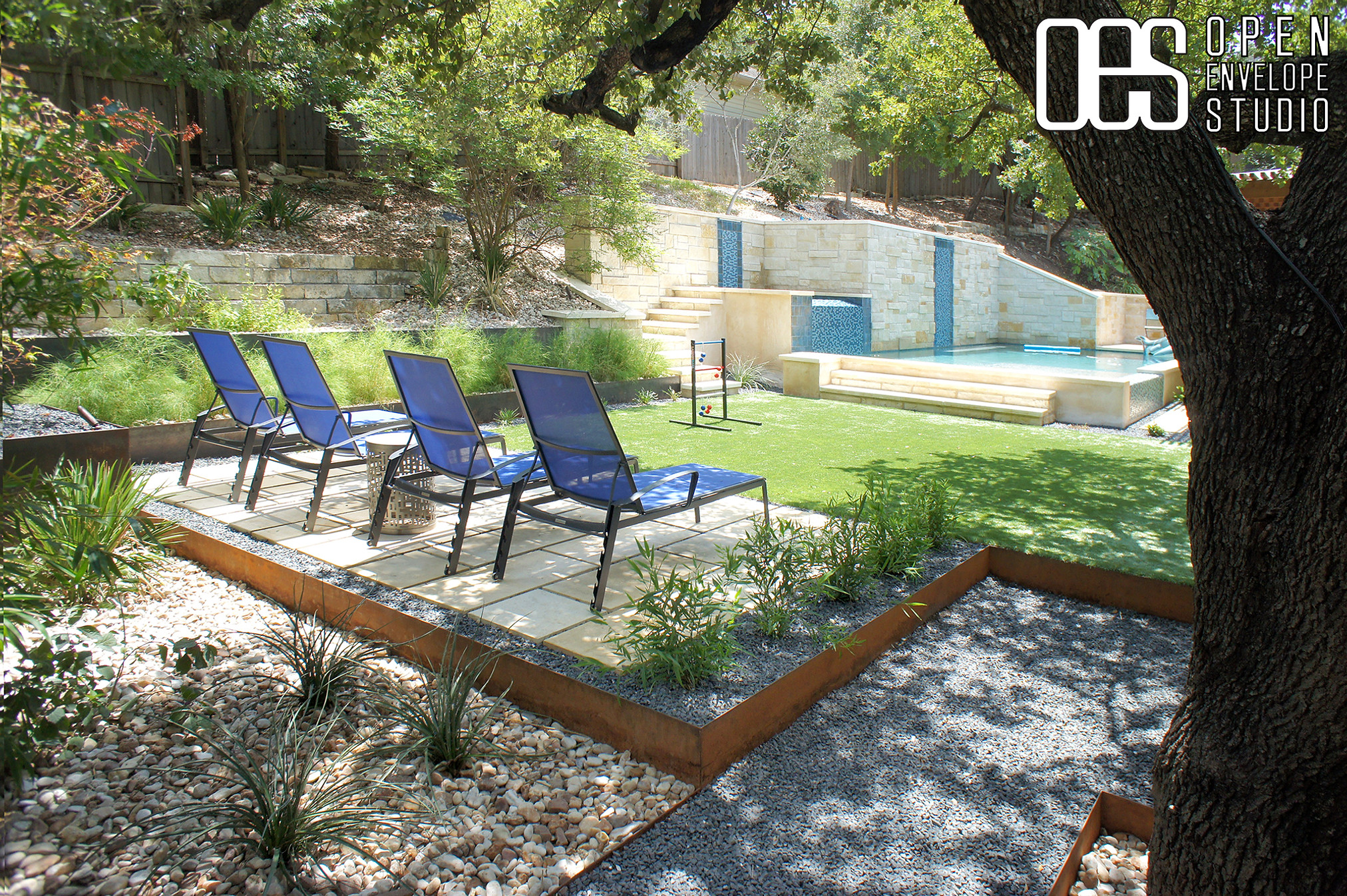 OES | steel-edged limestone paver patio, Texas basalt walkway, washed river stone planting beds, native plants, and artificial turf