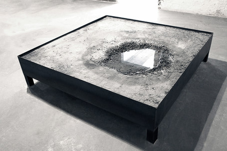 It is an artificial reproduction of a natural accident formed on the ground. It is a piece of relocated urban land, placed inside a space.