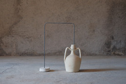 The series of sculptures reports the artist's investigation of the Catalan pre-Pyrenees mountains' landscape and population. Felipe selected traditional artefacts, which define the common idea attached to these areas, to compose visual storytellings. A roof tile, an amphora, a candle holder and a small jug are held together through iron strings. Conceptual and aesthetic connections interweave these objects.   On the one hand, these assemblages aim to interrogate how certain objects, made of local materials, create the local identity and history. On the other hand, they are also intended as art in Kantian terms: there is an aesthetic conversation between these objects. The artworks are connected to the artist's overall investigation about history and its role in a possible understanding of identity. He makes explicit his research with the following words: <<There is no way to understand ourselves, if it is not connected with social history and nature. In contemporary discourse, where we question so much identity and binary categories, we can deconstruct all these ideas only by looking back [to history].>>