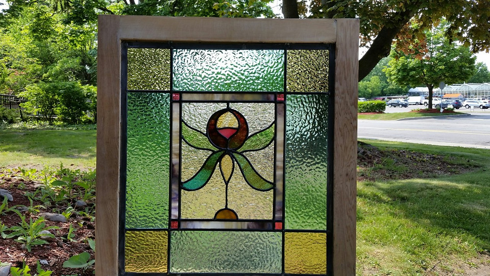 A window built from a combination of vintage and new glass, in an old frame