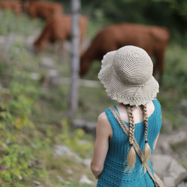 Little girl watching cows. Dressed in a knitted tunic, and crochet hemp hat. Knit & crochet designs by Prinser & Prinsesser. Available in store.