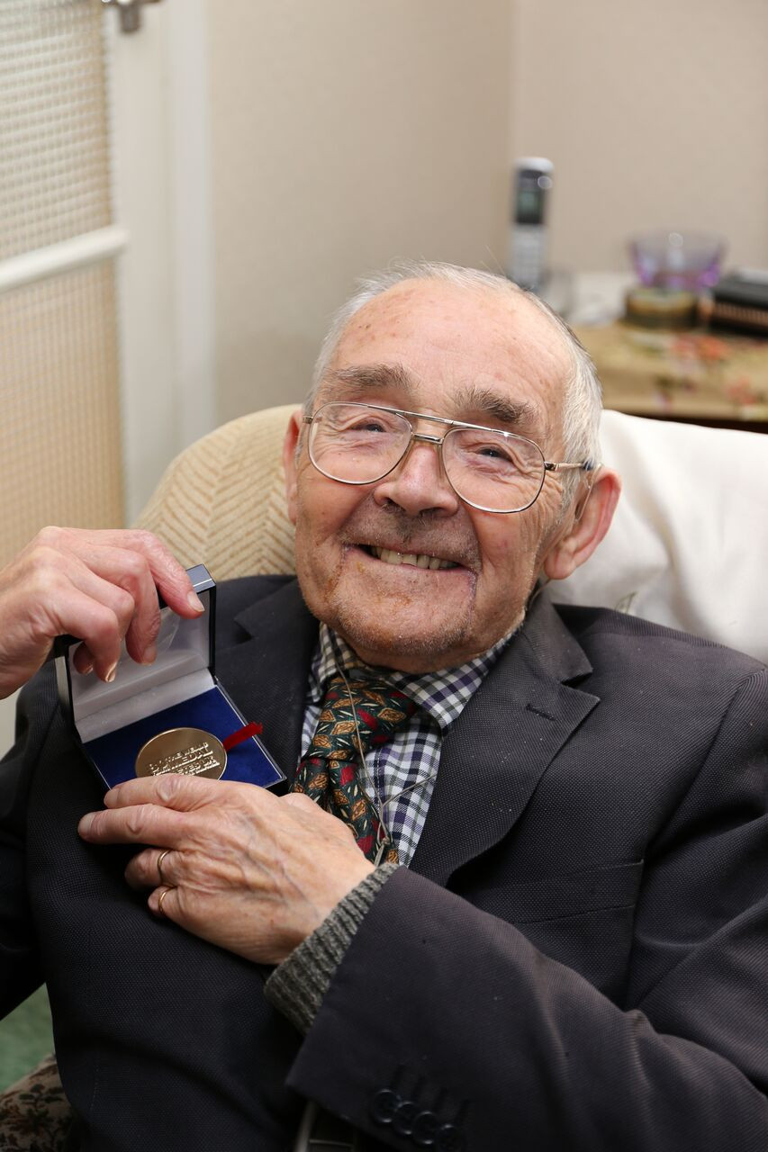 Clifford Whittaker being presented a medal from Diabetes UK