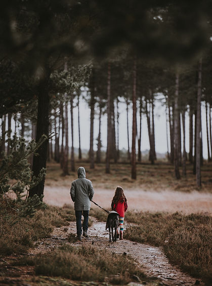 woman dog and child walking in wet fores