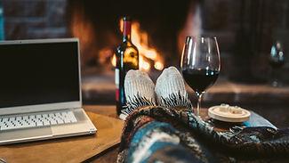 macbook-pro-beside-wine-glass-on-brown-w
