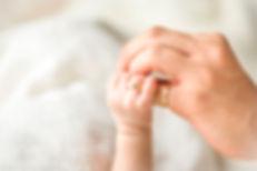 ママの手を握る赤ちゃんの指にベビーリング