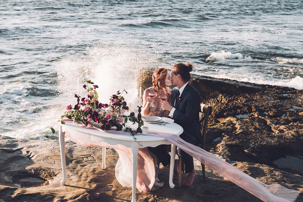 Moody and romantic deep purple and pink wedding flowers on a beautiful sweetheart table for two next to the Pacific Ocean at Sunset Cliffs in Point Loma by San Diego Wedding Florist, Le Champange Projects.