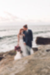 Romantic Sunset by the ocean. Couple snuggles up at Sunset Cliffs Elopement holding beautiful and lush bridal bouquet made by San Diego Wedding Florist Le Champagne Projects at Sunset Cliffs, San Diego.