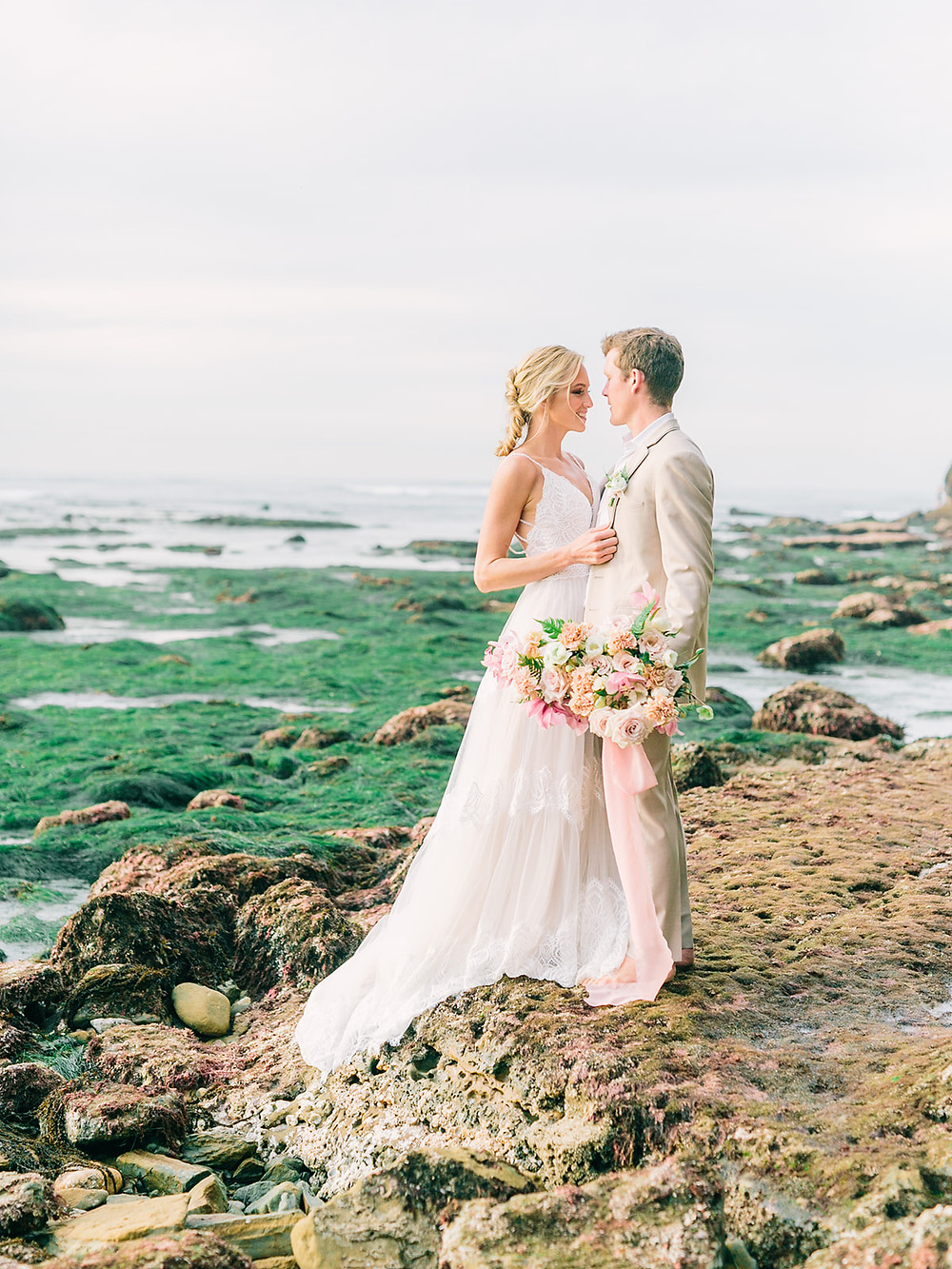 Beautiful lush and romantic Bridal Bouquet filled with Orchids, Roses & Hellebores for beach wedding What is more romantic that an oversized organic bouquet for a dreamy seaside wedding. This couple took their photos in the tide pools of Sunset Cliffs in San Diego, CA. Brides bouquet was lush and ethereal with a soft blush and pink palette for Spring of roses, orchids and carnations. #orchidbouquet #springweddingflowers #beachwedding #sandiegobeachwedding #sandiegoweddingflorist #sunsetcliffssandiego