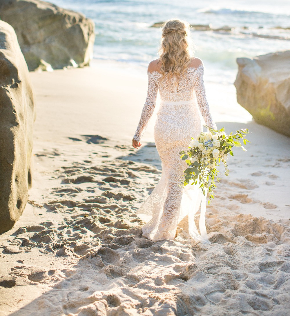 Bride in stunning off the shoulder lace dress holding eucalyptus and white rose bouquet made by San Diego Wedding and Elopement Florist, Le Champange projects at Windansea Beach Elopement in La Jolla, CA