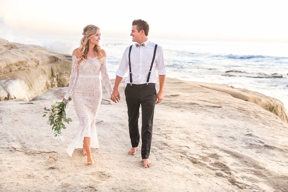 Groom with his Bride in stunning off the shoulder lace dress holding eucalyptus and white rose bouquet made by San Diego Wedding and Elopement Florist, Le Champange projects at Windansea Beach Elopement in La Jolla, CA