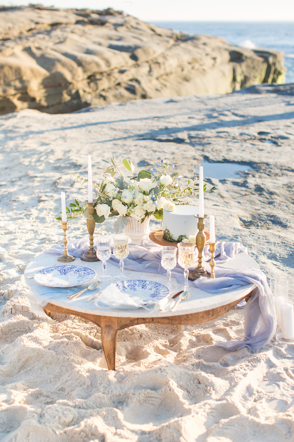 Intimate, romantic and elegant beach picnic setup for micro wedding or elopement with flowers by San Diego Wedding and Elopement Florist, Le Champagne projects at Windansea beach in La Jolla, CA. Eucalyptus and white roses paired with blue decor to mimc the ocean