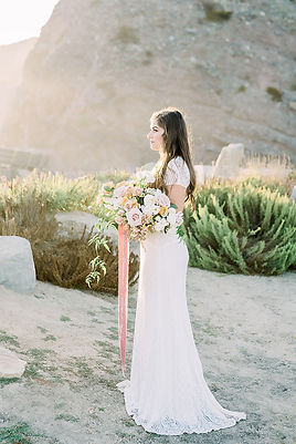 Romantic soft seaside lighting on bride holding lush organic bridal bouquet created by San Diego Wedding Florist Le Champage Projects