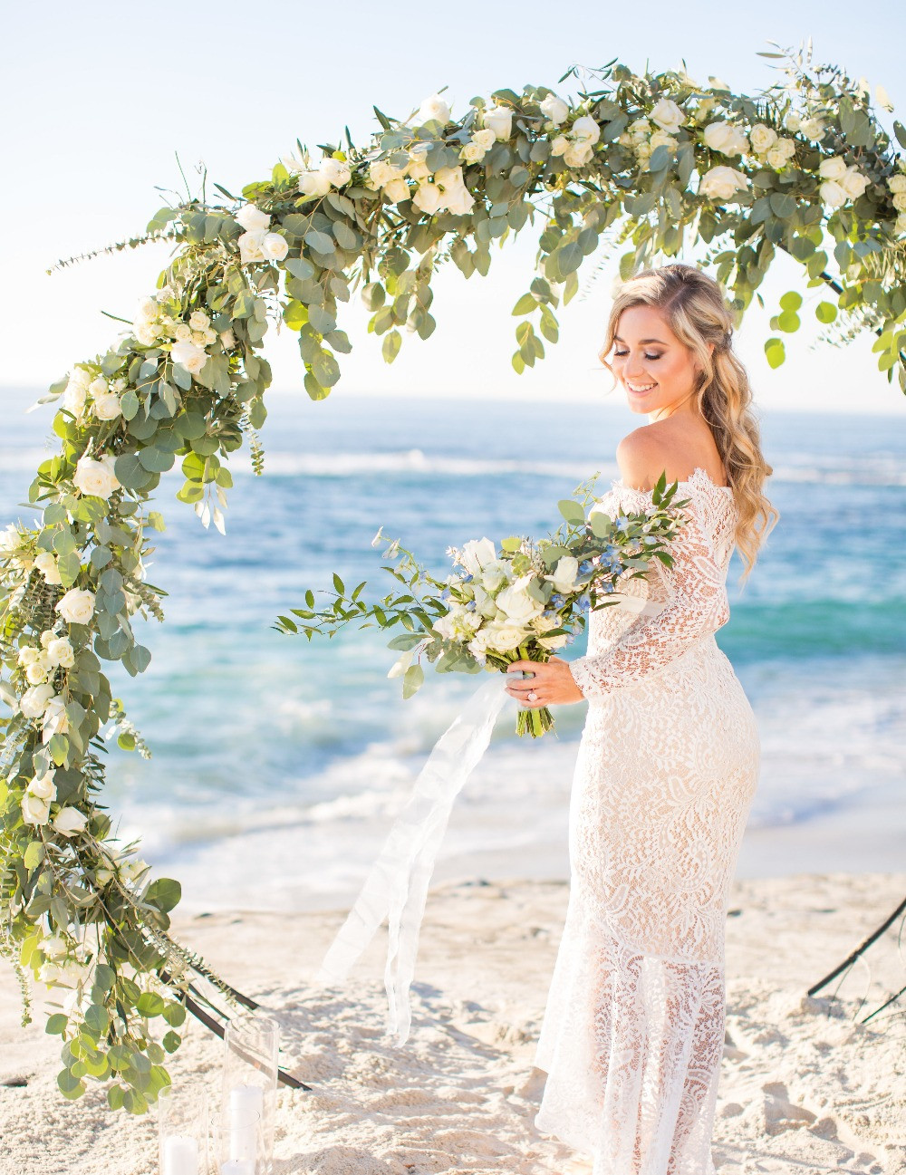 Bride in off the shoulder lace wedding dress stands under a beautiful full circle wedding arch with flowers by San Diego Wedding and Elopement Florist Le Champagne Projects. A full flower arch covered in eucalyptus and olive branches to create texture and white roses and spray roses to create simple elegance in front of the ocean at Windansea Beach in La Jolla CA.