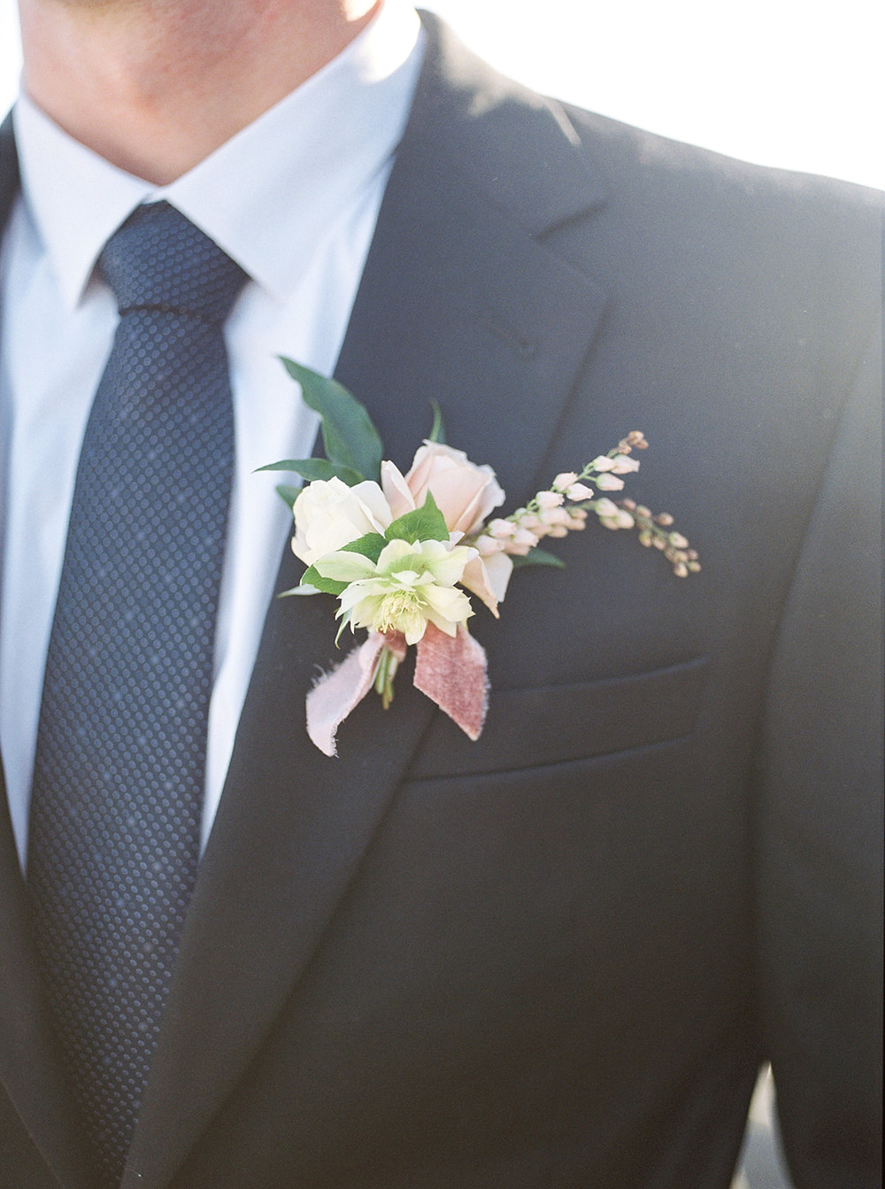 Soft and romantic boutonnière filled with hellebore, garden roses, and pieris for a late summer elopement on the beach in Dana Point by San Diego wedding florist Le Champange Projects tied with gorgeous velvet ribbon