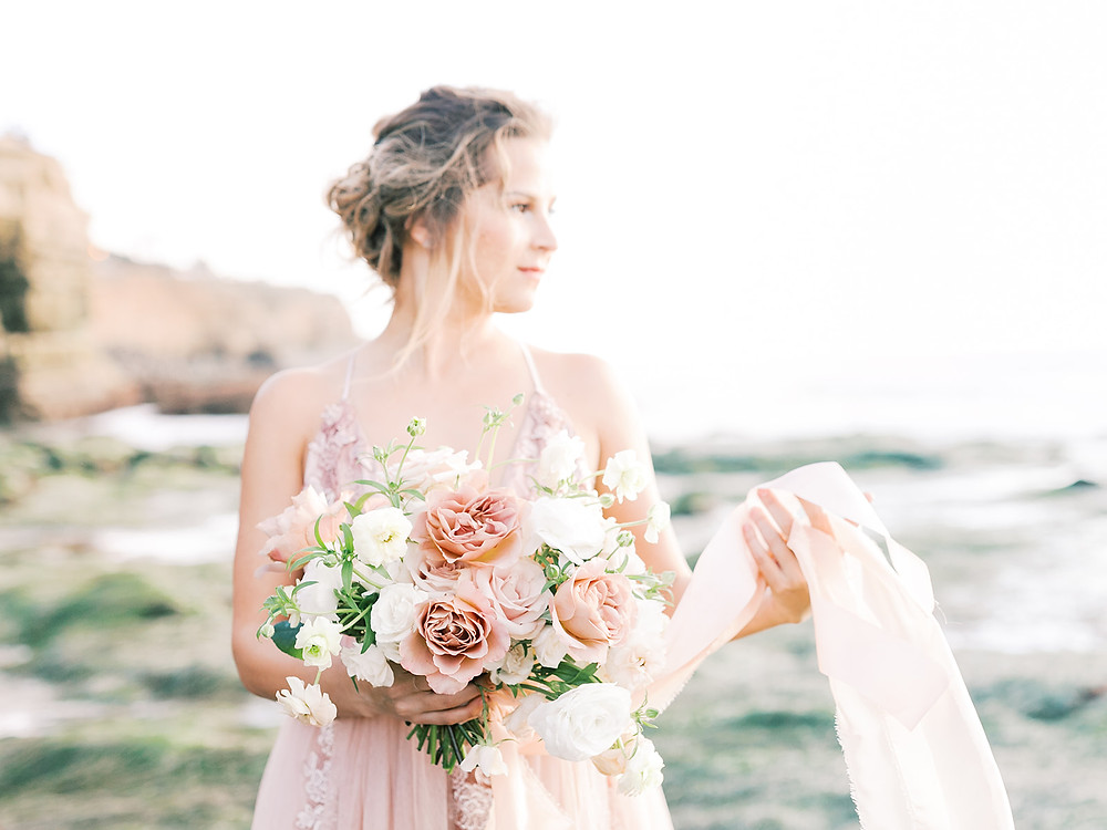 Beautiful organic garden style bridal bouquet by San Diego wedding florist Le Champagne Projects, held by bride in blush wedding dress at Sunset Cliffs, Point Loma, San Diego, CA