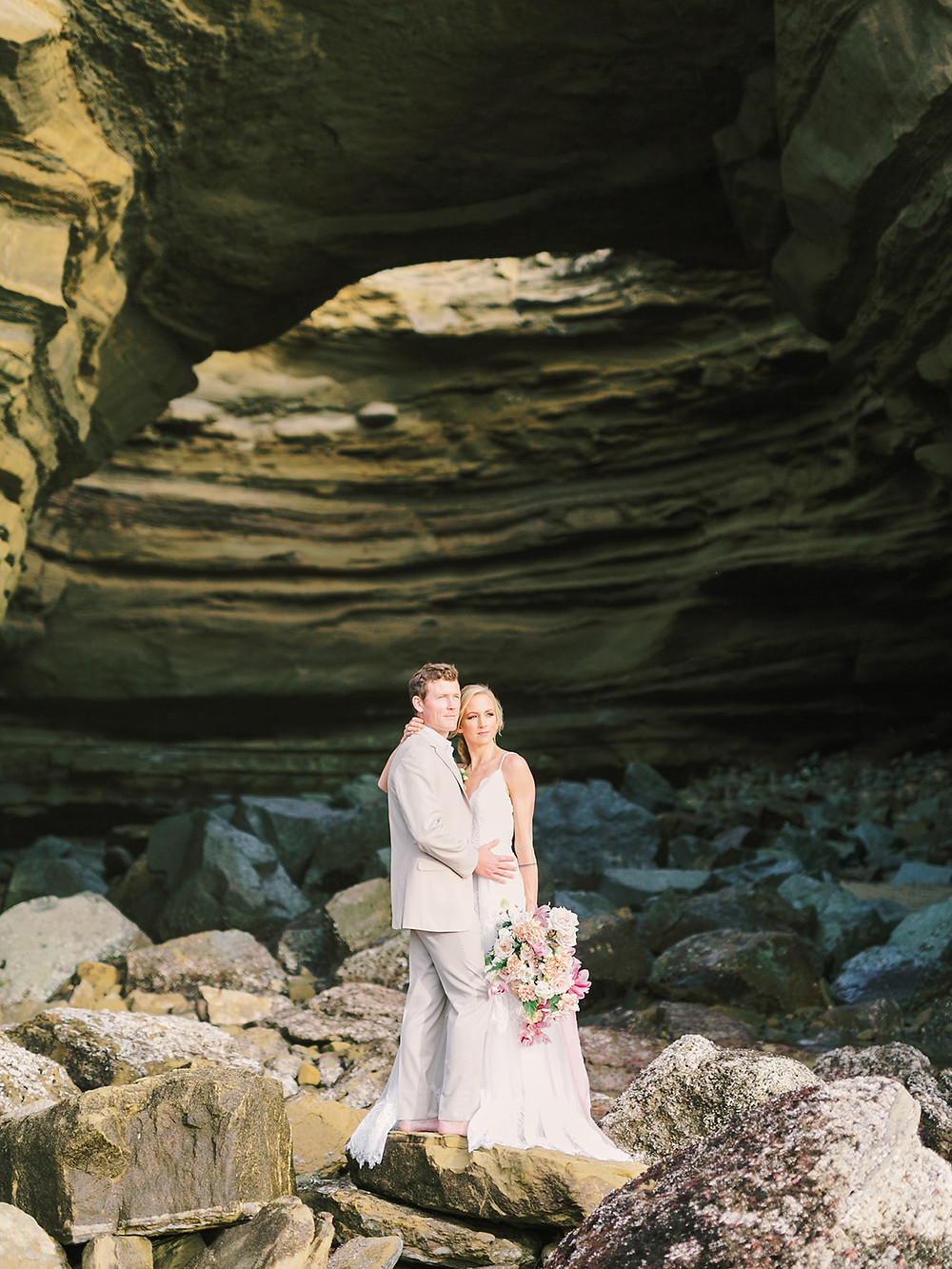 Sea Cave Elopement with Gorgeous Blush Bridal Bouquet This adventurous couple scaled down the cliffs at a rare low tide at Sunset Cliffs in San Diego, CA to take epic photos in the open air sea cave with a lush, organic blush bouquet filled with orchids, roses and hellebores made by San Diego wedding florist Le Champagne Projects. #adventurebrides #sunsetcliffs #sunsetcliffssandiego #sandiegobeachwedding #sandiegoweddingflorist #sandiegoweddingflorist
