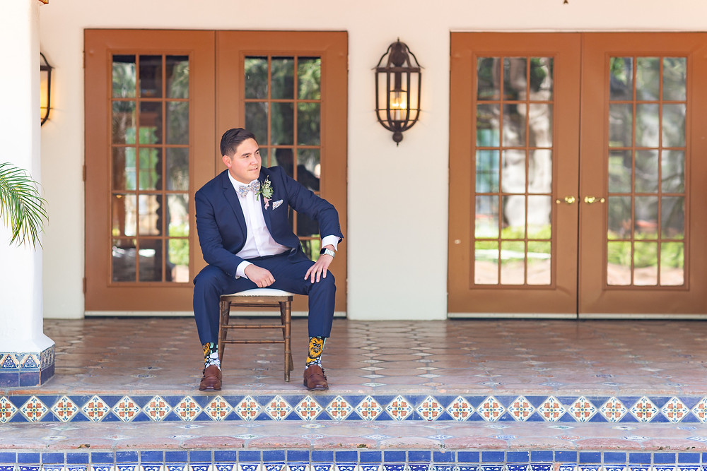Groom in cobalt blue tux with patterned tie and socks rocking his succulent, rosemary and lavender filled boutonnière for a purple colored wedding at Rancho Las Lomas in Orange County, CA made by San Diego Wedding Florist Le Champange Projects