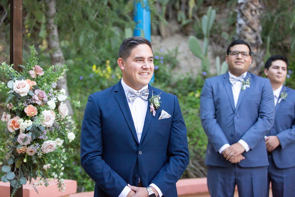 Groom next to Beautiful lush floral heavy purple ceremony arch;  filled with lilac, spirea, carnations, ranunculus, sweet peas, roses and butterfly ranunculus made by San Diego wedding florist Le Champange Projects for a stunning Spring wedding at Rancho Las Lomas in Orange County, CA with a purple color palette.