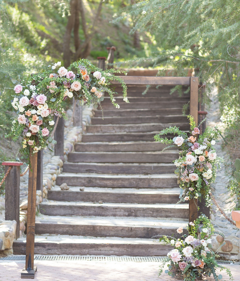 Beautiful lush floral heavy purple ceremony arch;  filled with lilac, spirea, carnations, ranunculus, sweet peas, roses and butterfly ranunculus made by San Diego wedding florist Le Champange Projects for a stunning Spring wedding at Rancho Las Lomas in Orange County, CA with a purple color palette.