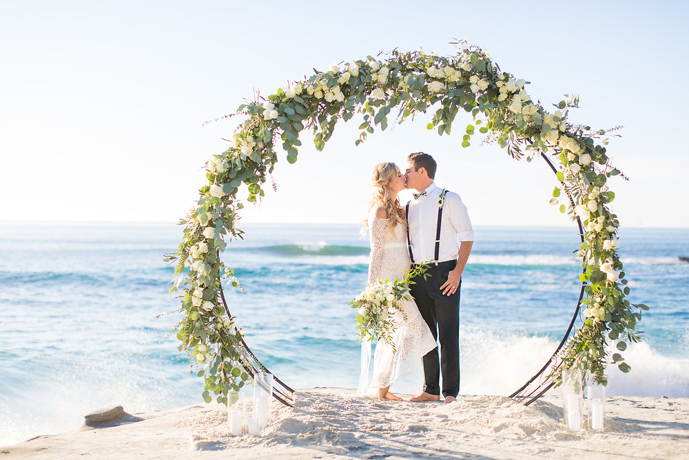 Couple stands under a beautiful full circle wedding arch with flowers by San Diego Wedding and Elopement Florist Le Champagne Projects. A full flower arch covered in eucalyptus and olive branches to create texture and white roses and spray roses to create simple elegance in front of the ocean at Windansea Beach in La Jolla CA.
