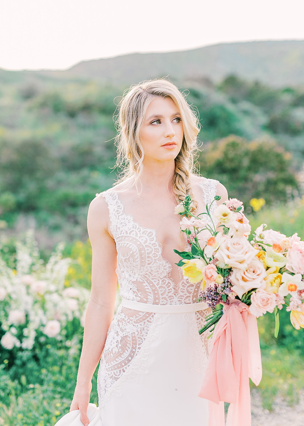 Beautiful dress from bridal boutique Bridal Showcase in north county San Diego. Bride holding lush and vibrant Spring bouquet filled with daffodils, lilac, tulips, butterfly ranunculus, etc, made by San Diego Wedding Florist, Le Champagne Projects