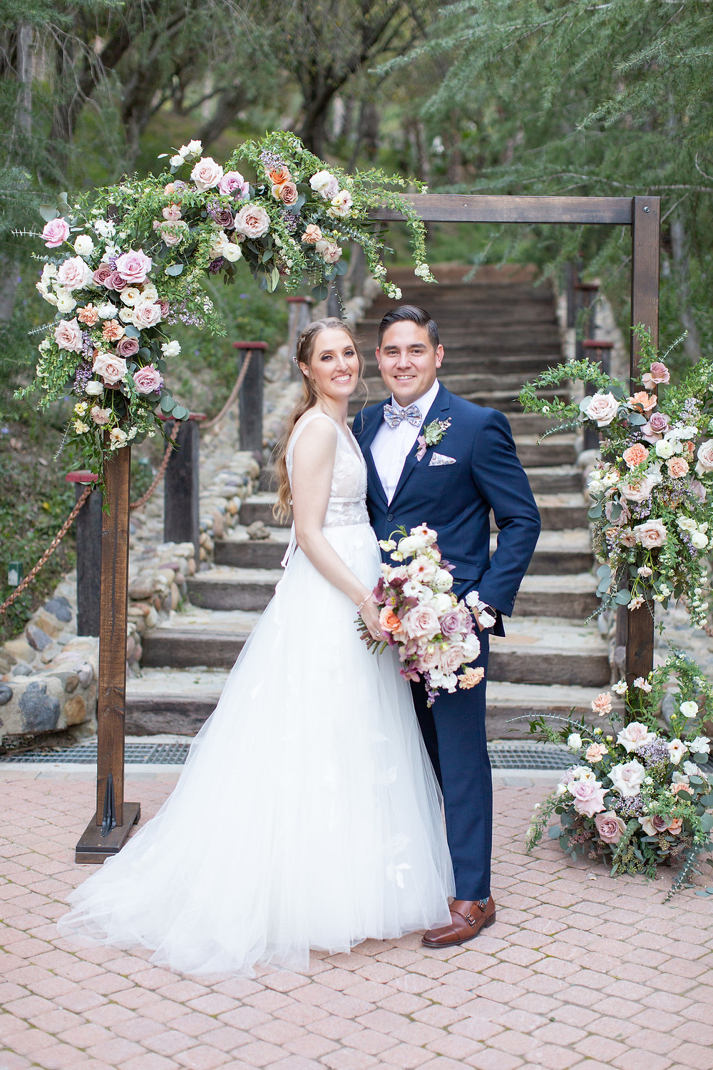 Bride and Groom under Beautiful lush floral heavy purple ceremony arch;  filled with lilac, spirea, carnations, ranunculus, sweet peas, roses and butterfly ranunculus made by San Diego wedding florist Le Champange Projects for a stunning Spring wedding at Rancho Las Lomas in Orange County, CA with a purple color palette.
