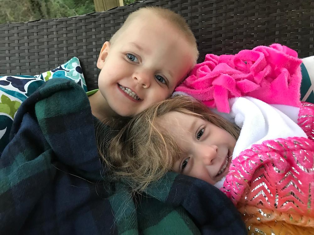 bundled up kids sitting on the swing