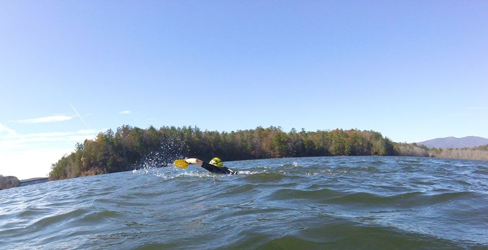 swimmer using paddles to swim across lake james in nc