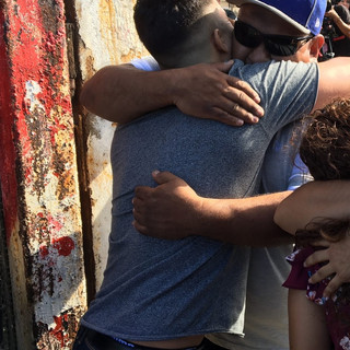 A brief embrace through an opening in the border wall