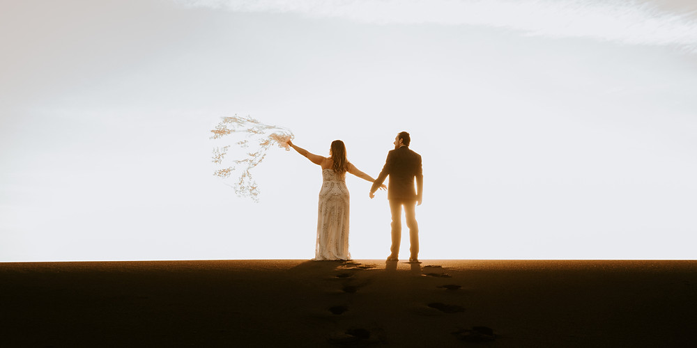 Woman and man in silhouette with sun rising standing on horizon