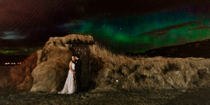 Man and woman embracing under Northern Lights at their Destination Wedding in Iceland will take your breath away